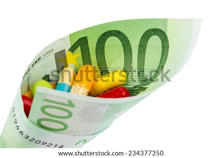 tablets and one hundred euro banknote symbol photo for charges for medicine and drugs the pharmaceutical industry - stock photo
