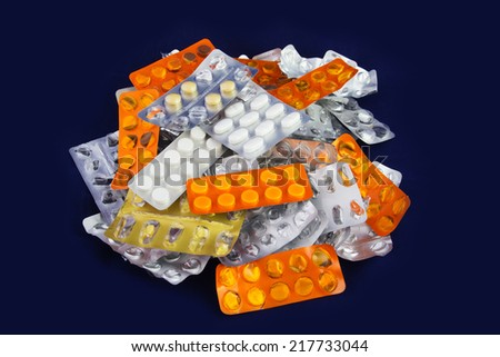 Tablets and Pills in Blister and Many Empty Pill Blister Packages. Isolated on a Blue Background. - stock photo