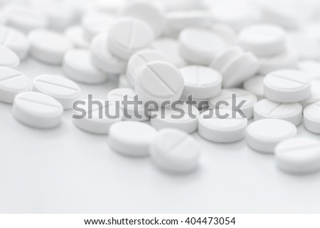 Tablets in white color in closeup. Bright white background. - stock photo