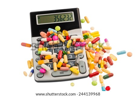tablets lie on a calculator. symbolic photo for costs in medicine and pharmaceutical industry - stock photo