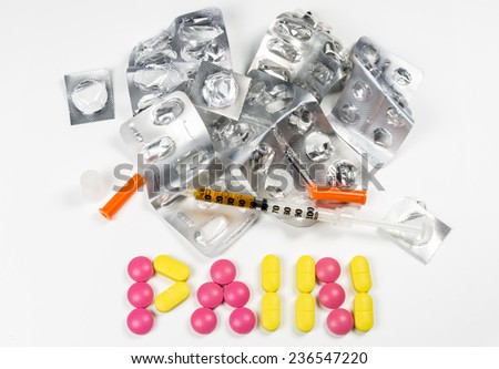 Tablets spelling pain with pile of empty packages - stock photo