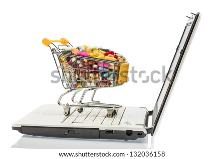 tablets with cart and computer. symbolic photo for the purchase of medicines on the internet - stock photo