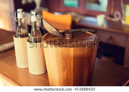 tableware and kitchenware concept - couple of bottles and wooden bucket with spoon on table at hotel room - stock photo