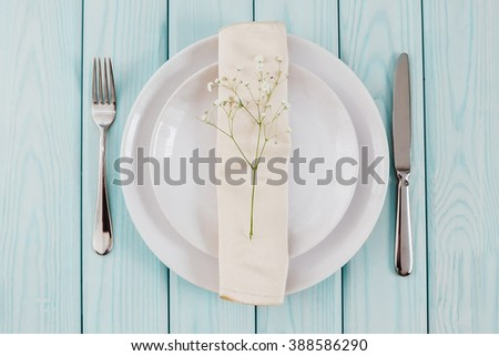 Tableware. Branch baby's breath on a napkin, and white plate with light wooden board. - stock photo