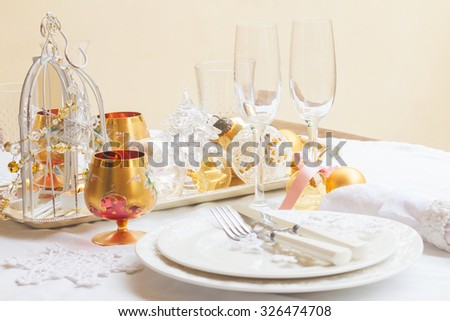 Tableware for christmas - plates, cups and utensils  with white table cloth and christmas golden decorations - stock photo