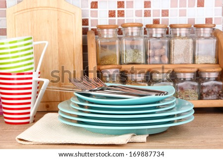 Tableware in kitchen on table on mosaic tiles background - stock photo