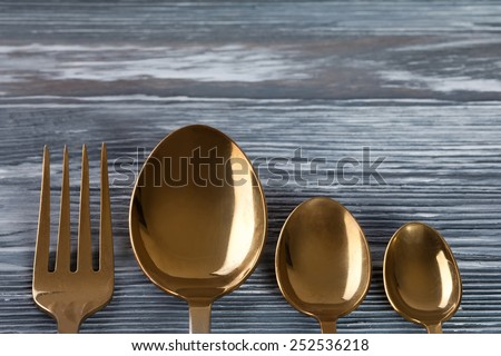 Tableware set (golden spoons and fork)  on the gray wood background. scratches and scrapes. Soft focus. - stock photo
