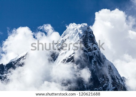 Taboche mountain in Himalayas, Nepal. Mountains landscape over blue sky and clouds - stock photo