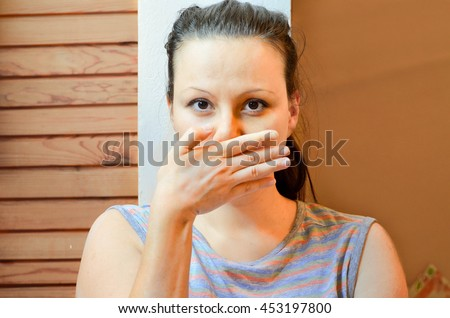 Taboo topic and freedom of speech concept. Woman with hands over her mouth. - stock photo