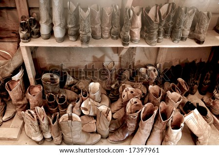Tack Room full of  Well Worn Cowboy Boots - stock photo