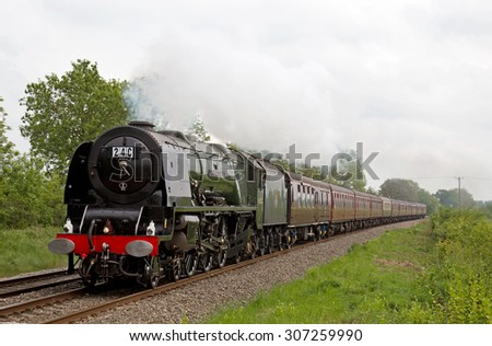 TACKLEY, UK - MAY 23: Ex LMS Princess Coronation class steam loco Duchess of Sutherland heads north through rural Oxfordshire with a special steam charter excursion train on May 23, 2015 in Tackley