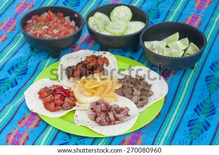 Taco plate display of four corn tortillas with different kinds of barbecued meat and onion with condiment bowls of fresh Mexican salsa, cucumbers, and limes on a decorative blue tablecloth - stock photo