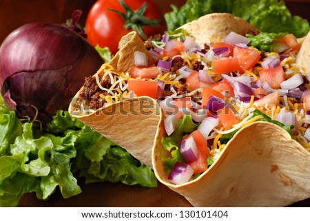 Taco salad in freshly baked flour tortilla bowl (seasoned ground beef, lettuce, onions, tomatoes, and shredded cheese) with tomato, onion, and leaf lettuce in background.  Macro with shallow dof. - stock photo