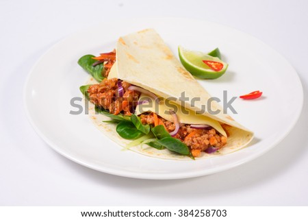 Tacos on a white plate on a white background served with lime