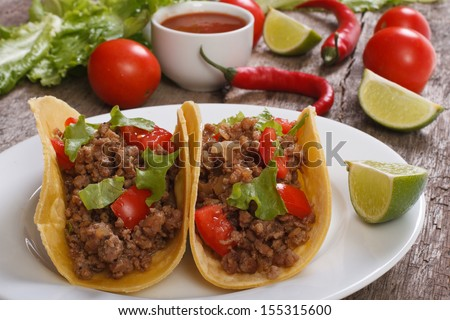 Tacos stuffed with ground beef with vegetables and chili sauce on a wooden table - stock photo
