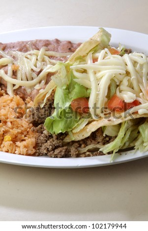 Tacos / Traditional Mexican plate. Beef tacos topped with lettuce and tomatoes. with a side of rice and beans.