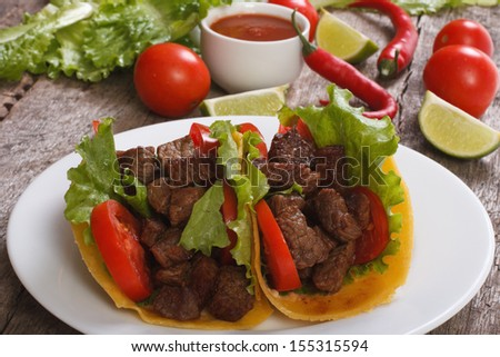 Tacos with chilli sauce and vegetables on a wooden table - stock photo