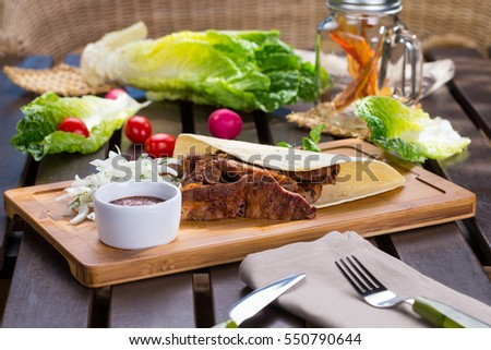 Tacos with meat  and onion on cutting board with tomato and green lettuce on wooden table.