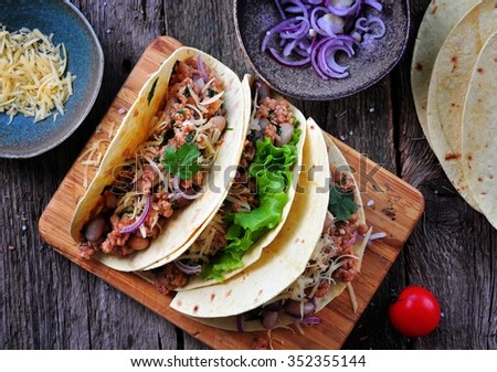 tacos with minced meat with beans, cheese and onion - stock photo