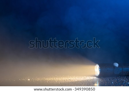 Tactical waterproof flashlight with waterdrops and fog or steam - stock photo