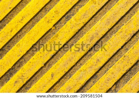 Tactile paving slab texture. A paving tile of yellow color with raised diagonal lines - stock photo