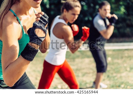 Taebo team doing uppercuts in training, selective focus - stock photo