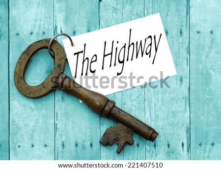 Tagged vintage brass key on turquoise wooden background with concept of phrase key to the highway - stock photo