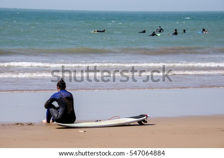 TAGHAZOUT, MOROCCO - MARCH 01, 2016: Young woman sitting on beach sand next to her surfboard, with defocused background, sea and other surfers on the boards