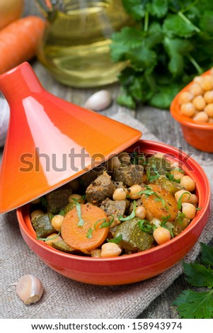 tagine with beef, chickpeas, vegetables and herbs, close-up, vertical