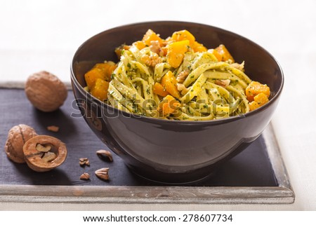 Tagliatelle noodles with pumpkin, walnuts and basil pesto - stock photo
