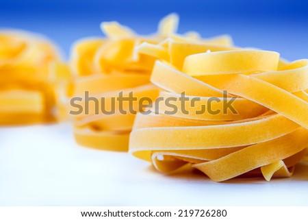 Tagliatelle pasta on white blue background.Macro concept. Italian Mediterranean cuisine.  - stock photo