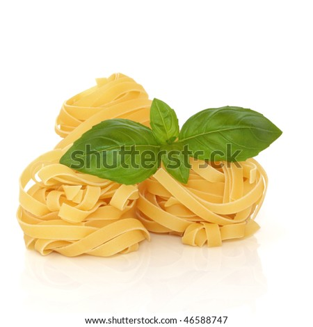 Tagliatelle pasta with basil herb leaf isolated over white background with reflection.
