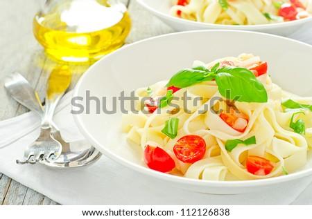Tagliatelle pasta with cherry tomato and basil - stock photo