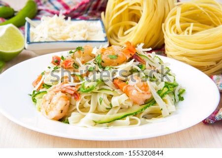 Tagliatelle pasta with fried shrimps, cheese Parmesan, parsley and zucchini ribbons, handmade dish - stock photo