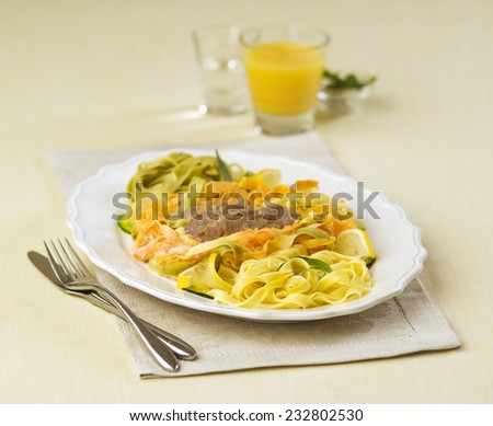 tagliatelle pasta with meat on a white plate with orange juice in the background - stock photo
