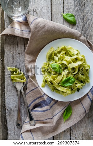 Tagliatelle pasta with pesto sauce and basil leafs on white plate, wood background, top view - stock photo
