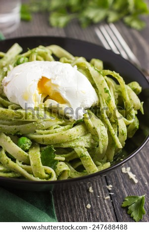 Tagliatelle pasta with spinach and green pea pesto and poached egg - stock photo