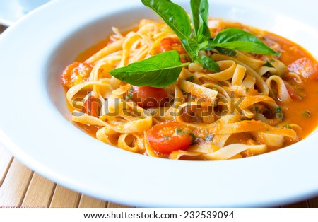 Tagliatelle pasta with tomato sauce and basil. Italian cuisine. - stock photo