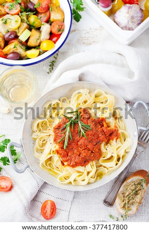 Tagliatelle pasta with tomato sauce and red pesto Italian cuisine Top view - stock photo