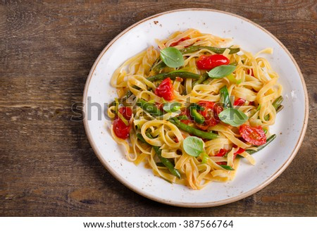 Tagliatelle pasta with vegetables on  wooden background. Top view