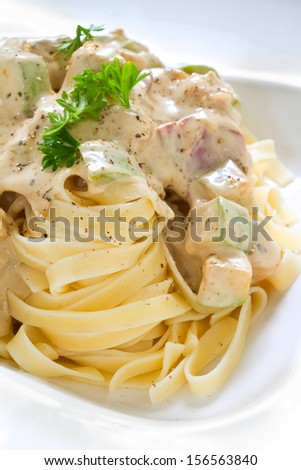 Tagliatelle pasta with white chicken zucchini sauce. Studio shot - stock photo