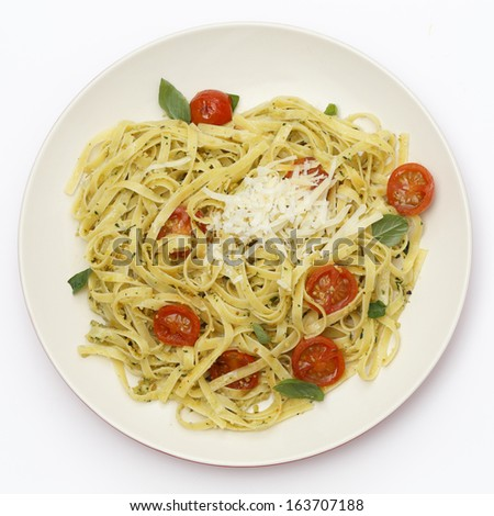Tagliatelle ribbon pasta tossed with a green, basil pesto and grilled cherry tomatoes, garnished with basil leaves, topped with fresh-grated parmesan, viewed from above.  - stock photo