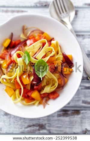 Tagliatelle with peppers, red onion and basil  - stock photo