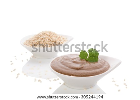 Tahini pasta and sesame seeds in white bowl isolated on white background. Hummus ingredients, mediterranean eating. - stock photo
