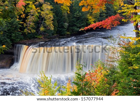 Tahquamenon Falls in Michigan's eastern Upper Peninsula seen with colorful fall foliage. This beautiful waterfall is said to be the second largest in the United States east of the Mississippi River. - stock photo