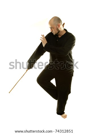 Tai Chi chuan man is practicing martial art with wooden staff - stock photo