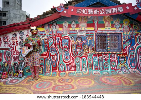 TAICHUNG, TAIWAN - FEB 16: Street performer plays guitar in front of the colorful graffiti painted in the whole Rainbow village on Feburary 16, 2014. It becomes a famous sightseeing spot in Taiwan.