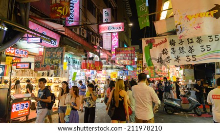 TAICHUNG, TAIWAN - JULY 12: Pedestrians at a Fengjia Night Market JULY 12, 2014 in Taichung, TW. Night markets are an important part of the culinary culture of Taipei. - stock photo