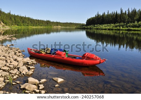Taiga river Paga, Russia, the Polar Urals. Virgin Komi forests, red boat on the river.