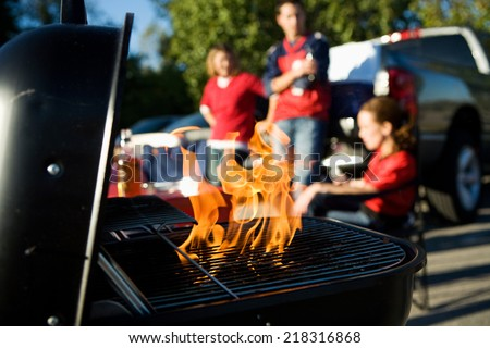 Tailgate: Charcoal Burning In Grill During Tailgating Party - stock photo